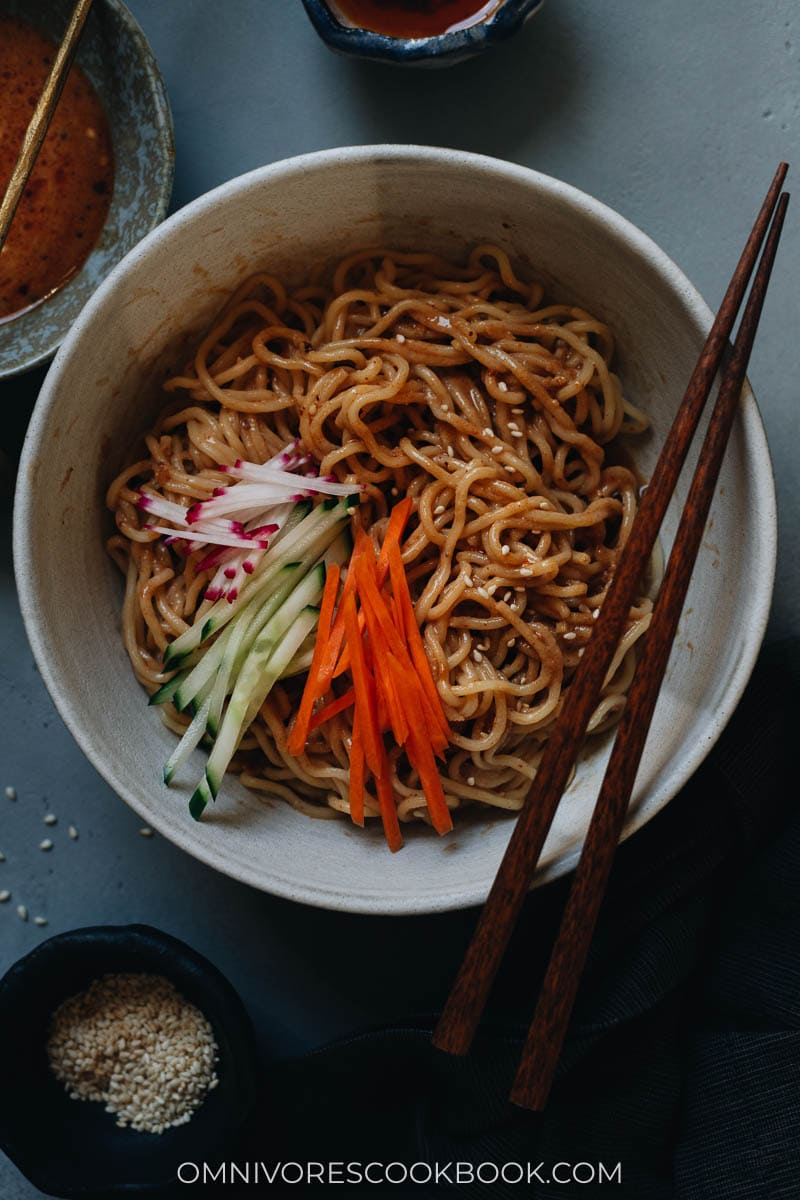Chinese sesame noodles in a bowl with cucumber and radish