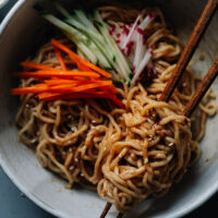 Chinese noodles in a bowl with sesame sauce and vegetables