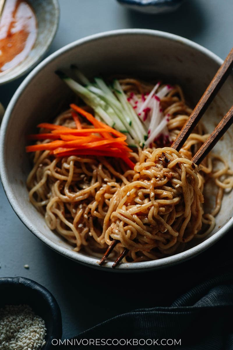 Closeup of nutty Chinese noodles in a bowl with chopsticks