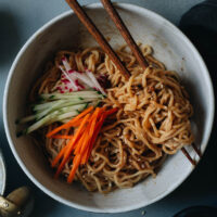 Sesame noodles is a perfect dish for a hot summer night when you don't feel like standing in front of a hot stove. The nutty savory sauce that has a hint of sweetness and spiciness, it's always a crowd pleaser. You can simply serve it without any toppings as a side dish. You top it with fresh summer produce and serve it as an appetizer for your grilling party. Or you can load it up with more toppings to serve it as a main.