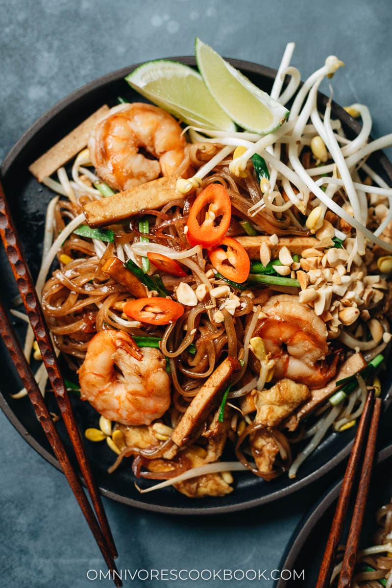 Easy shrimp fried noodles with egg and tofu, peanuts, chili pepper, and lime